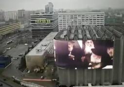 מיוחד: מסך ענק המקרין קטעי וידאו מהרבי מוצב כעת ברחוב מרכזי במוסקבה, על קיר אולם האירועים שבו תתקיים חתונת בתו של הרב והשליח הראשי הרב בערל לאזאר. צפו