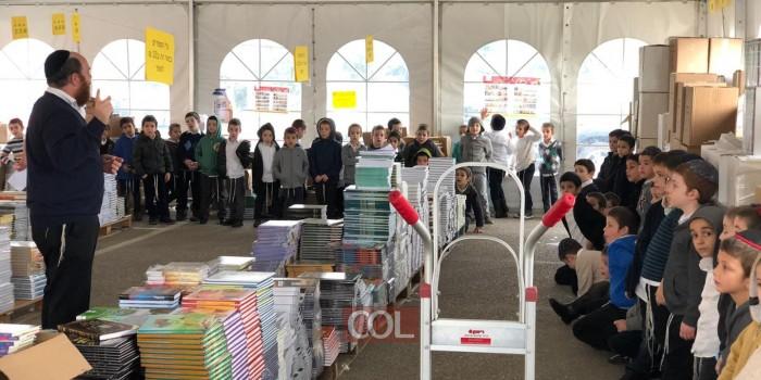 כיתה ג׳ חיידר אידיש ׳אהלי תורה׳ מקבלים מהמורים יהודה קוזלובסקי ולוי סוסובר סקירה על חג הספרים ׳דידן נצח׳ באוהל המכירות של הוצאת הספרים קה״ת בכפר חב״ד