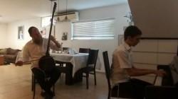 המוזיקאי נאור כרמי מנגן יחד עם בנו את ניגון חג הגאולה