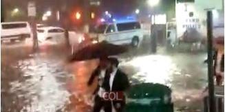 עם מטרייה ומגפיים, מים עד הברכיים: בחורים צועדים בשדרת איסטרן פארקווי ממול 770, בכביש שהפך ל'נהר' בעקבות השטפונות העזים מסופת ההוריקן